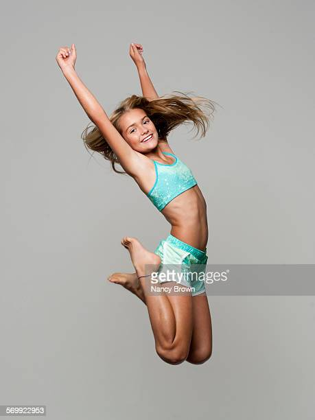 Caucasian eleven year old girl jumping for joy