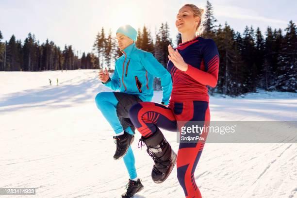 kaukasische ethnische zugehörigkeit mann und frau tun skips vor dem skifahren an einem berg - aufwärmen stock-fotos und bilder