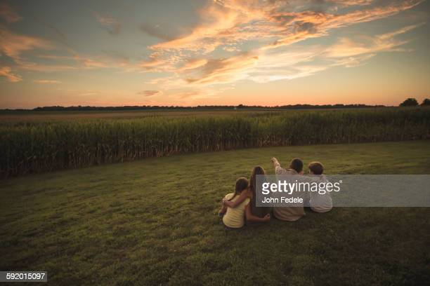 Caucasian family admiring corn fields at sunset