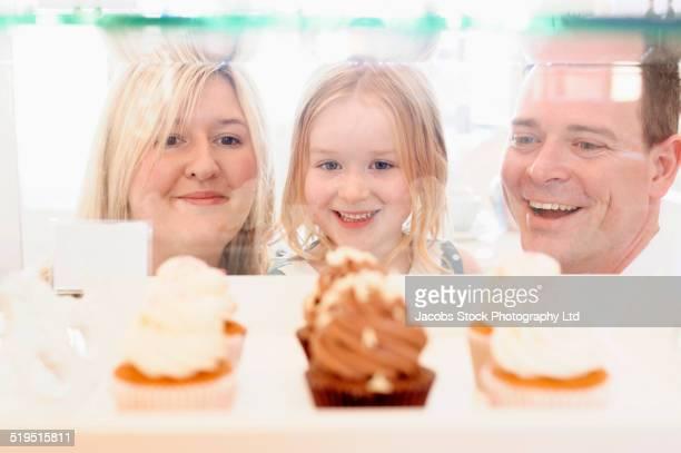 Caucasian family admiring cupcakes in bakery window
