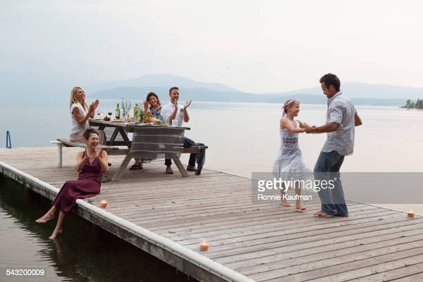 caucasian family cheering as father and daughter dance on pier over lake - molo foto e immagini stock