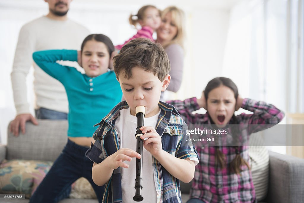 Caucasian family covering ears with boy playing recorder : Stock Photo