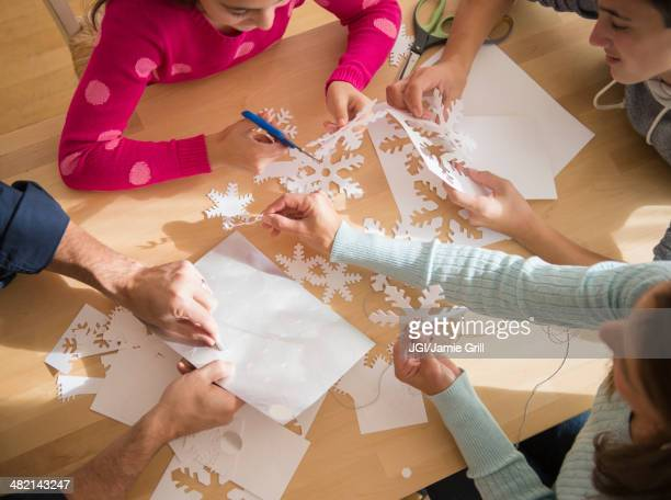 Caucasian family cutting out paper snowflakes