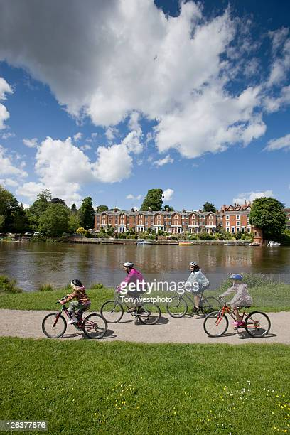 caucasian family cycling in the meadows by river dee, chester, uk - cheshire england stock pictures, royalty-free photos & images