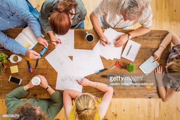 Caucasian family designing dresses on paper on wooden table
