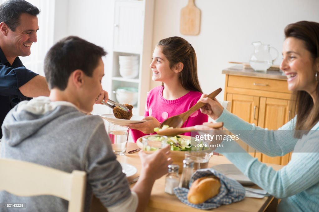 Caucasian family eating at table : Stock Photo