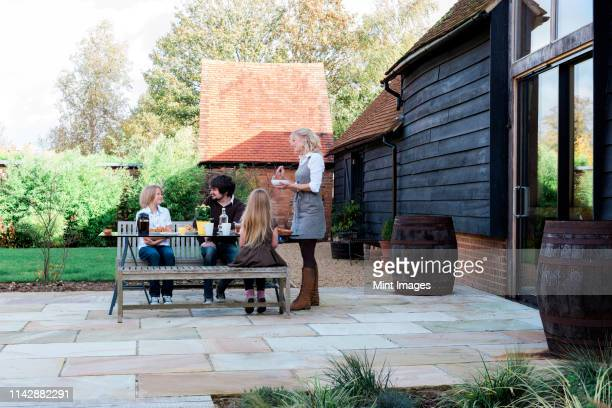 caucasian family eating breakfast in backyard - garden decking stock pictures, royalty-free photos & images