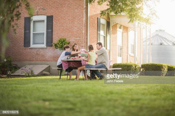 Caucasian family eating in backyard