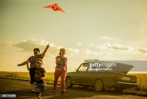 Caucasian family flying kite on rural road