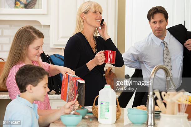 caucasian family having breakfast in kitchen - urgency stock photos and pictures