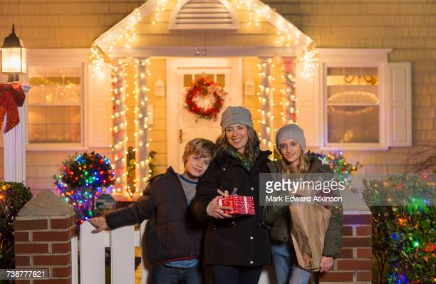 Caucasian family holding Christmas gifts on front stoop