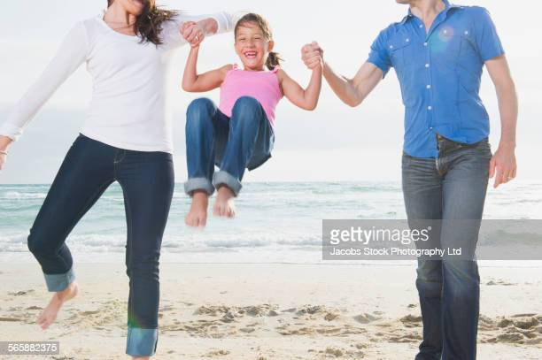 caucasian family holding hands and swinging daughter on beach - midsection stock pictures, royalty-free photos & images