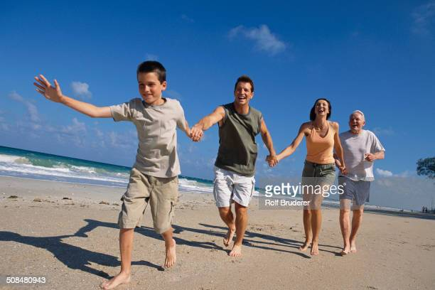 Caucasian family holding hands on beach