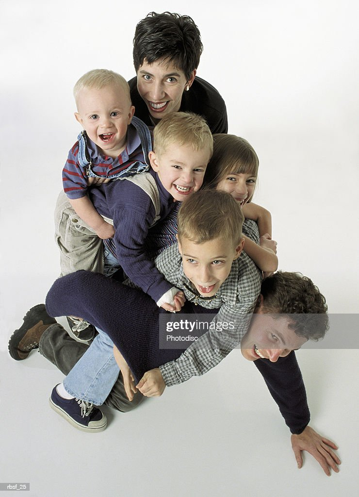caucasian family of six with brown and blonde hair with the kids laughing pilled on top of dad with mom behind them : Foto de stock