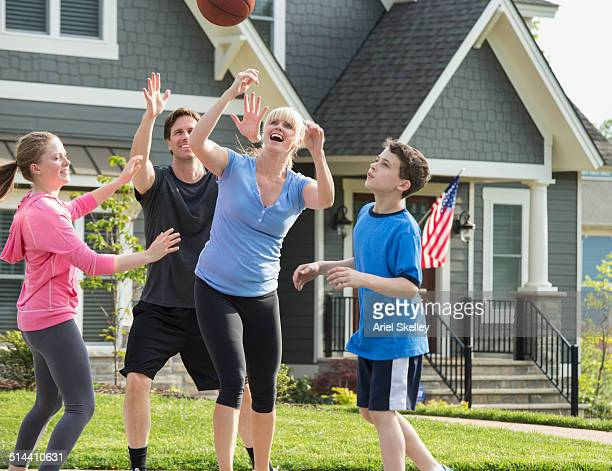 Caucasian family playing basketball together