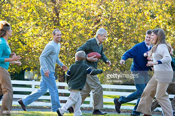 caucasian family playing football together outdoors - family reunion stock pictures, royalty-free photos & images