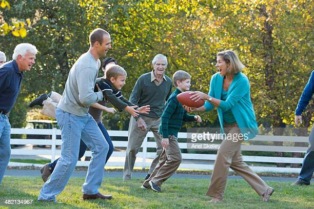 Caucasian family playing football together outdoors