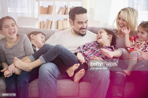 caucasian family playing on sofa - fazendo cócegas - fotografias e filmes do acervo
