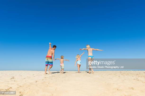 Caucasian family playing together on beach