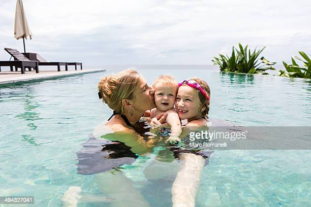 Caucasian family relaxing in infinity pool