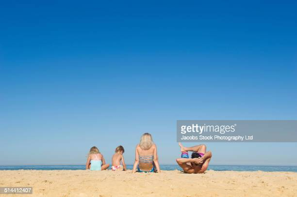 Caucasian family relaxing together on beach