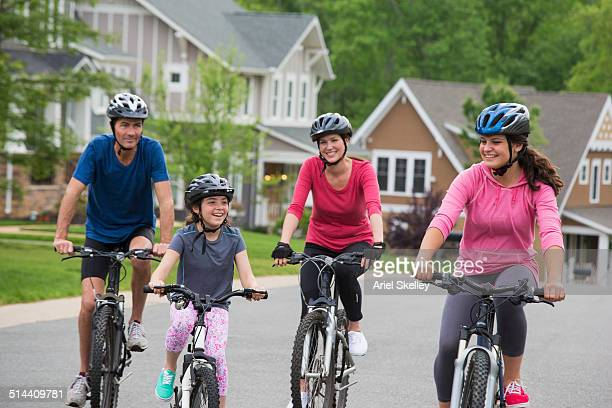 Caucasian family riding bicycles on suburban street