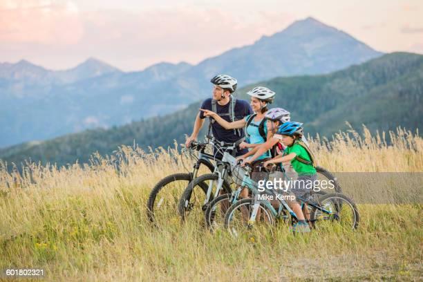 Caucasian family riding mountain bikes in field