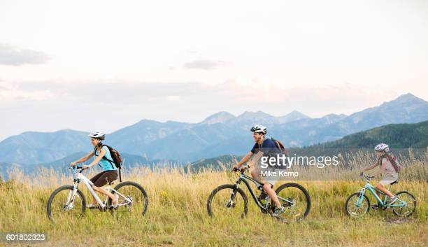 caucasian family riding mountain bikes in field - family with one child stock pictures, royalty-free photos & images