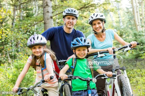 Caucasian family riding mountain bikes