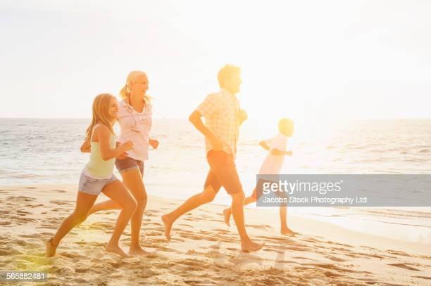 Caucasian family running on beach