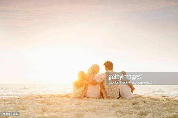 Caucasian family sitting on beach