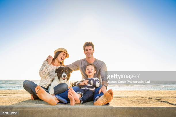Caucasian family sitting with dog on beach