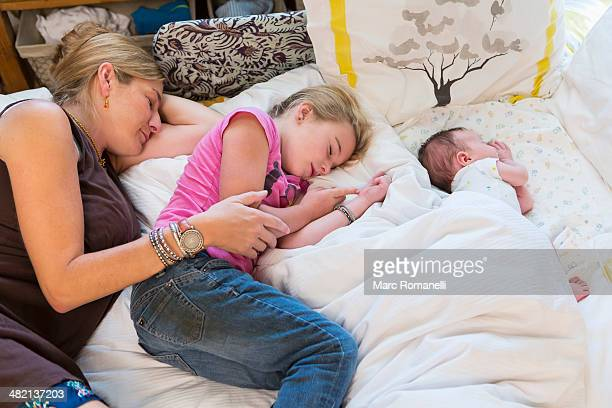 Caucasian family sleeping on bed