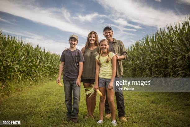Caucasian family smiling in corn field
