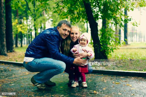 Caucasian family smiling on rainy path in park