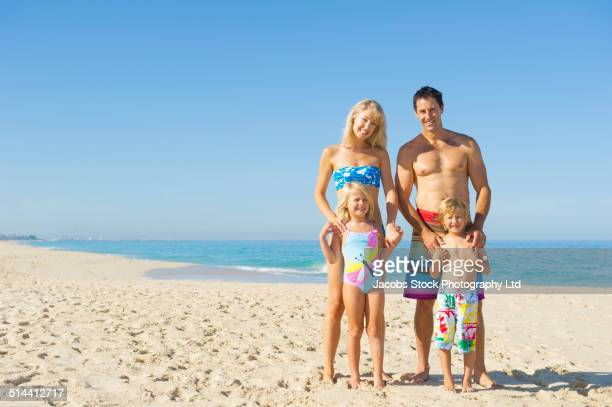Caucasian family smiling together on beach