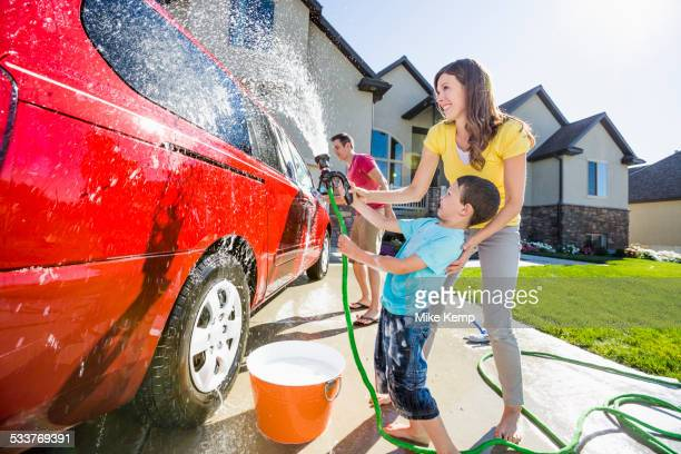 Caucasian family spraying water on car in driveway