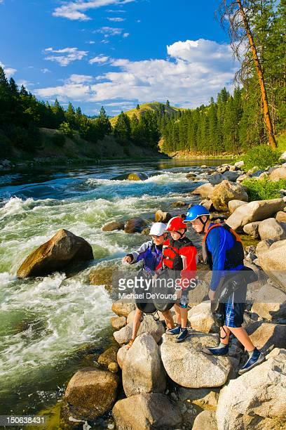 Caucasian family standing on rocks near river