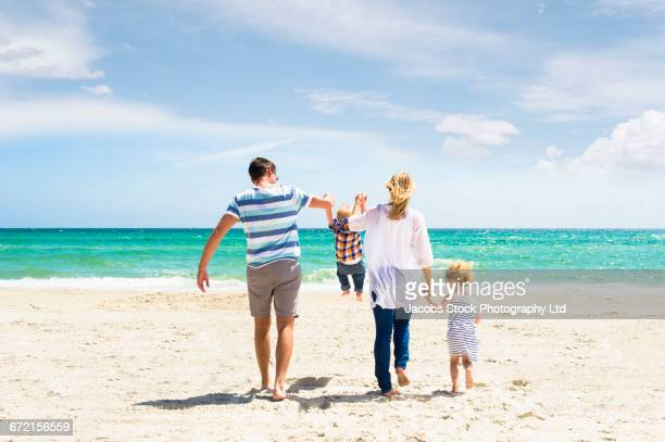Caucasian family swinging son by arms at beach
