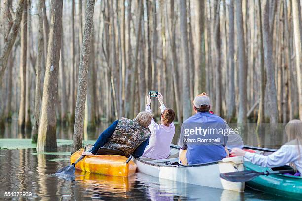 Caucasian family taking cell phone photographs in canoes on river