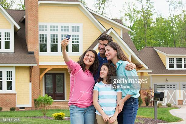 Caucasian family taking pictures of themselves outside house