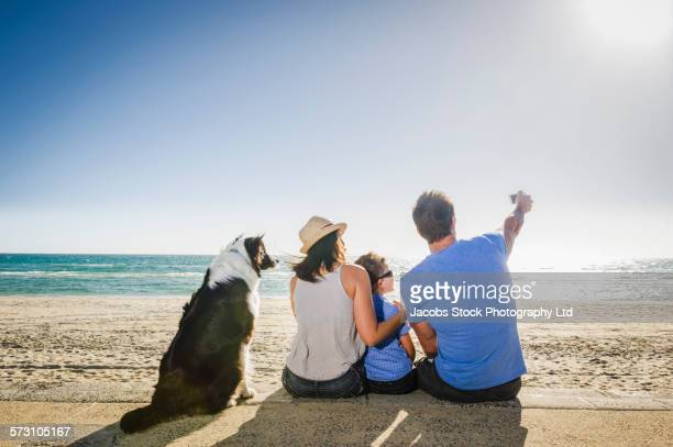 Caucasian family taking selfies with dog on beach