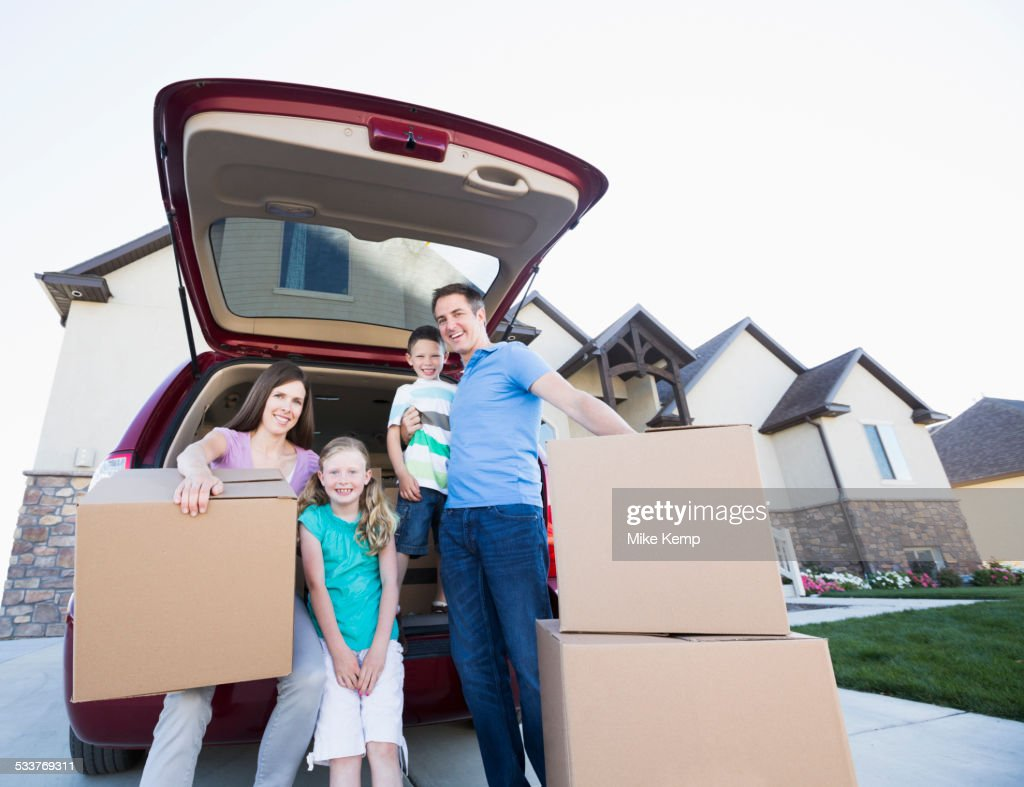 Caucasian family unpacking cardboard boxes from car : Foto stock