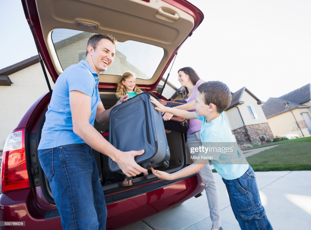 Caucasian family unpacking suitcases from car : Foto stock