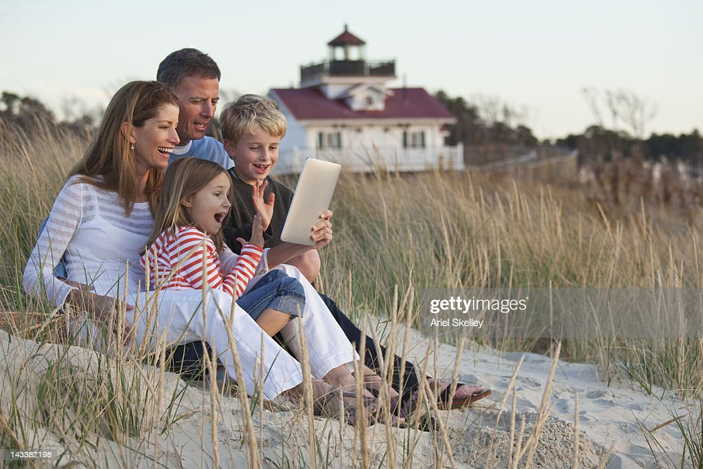 Caucasian family using digital tablet on beach : Stock Photo