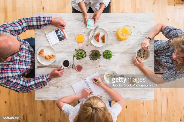 Caucasian family using technology at breakfast table