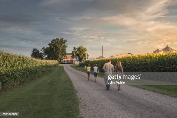 Caucasian family walking on dirt path by corn field