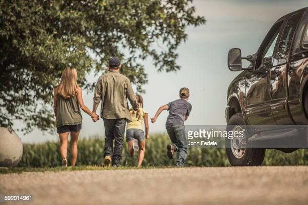 Caucasian family walking on farm
