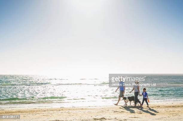 Caucasian family walking with dog on beach