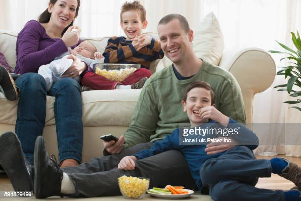 Caucasian family watching television in living room